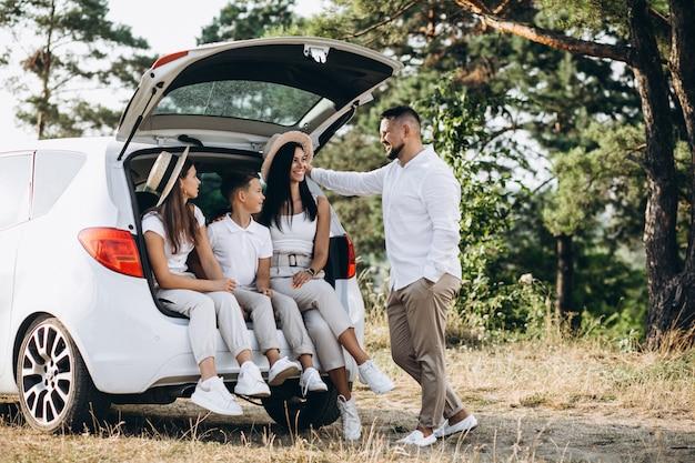 Padres con sus hijos en auto en el campo Foto gratis