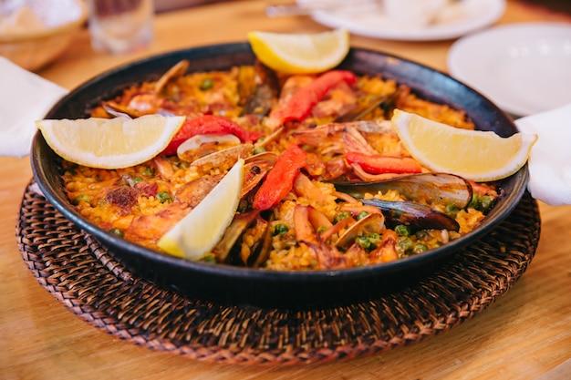 La paella incluye arroz de grano corto, habas, gambas, perna viridis y almejas. Foto Premium