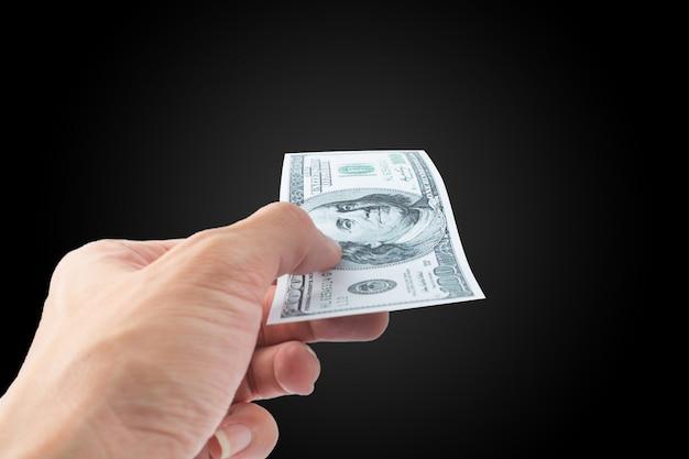 Pagar dinero billete de dólar sobre fondo negro Foto Premium