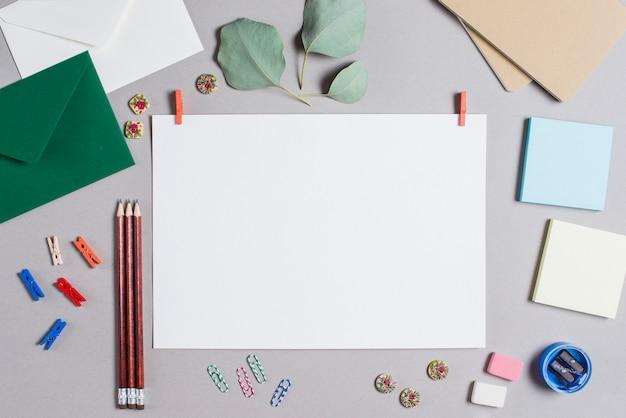 Página en blanco en blanco con clavija de ropa rodeada de papelería sobre fondo gris Foto gratis