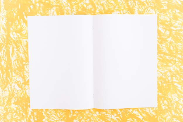 Página en blanco blanco sobre fondo amarillo con textura Foto gratis