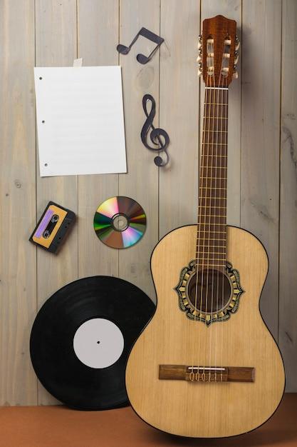 Página musical en blanco; casete; disco compacto; y nota musical pegada en pared de madera con guitarra y vinilo. Foto gratis