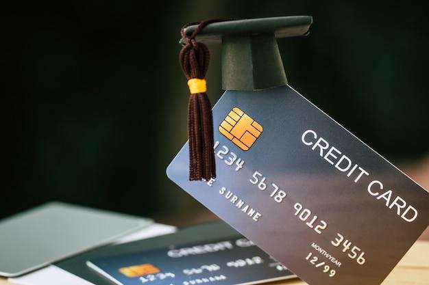 Pago de la educación tarjeta de crédito para el estudio concepto de graduación: límite de graduación en la tarjeta simulada Foto Premium