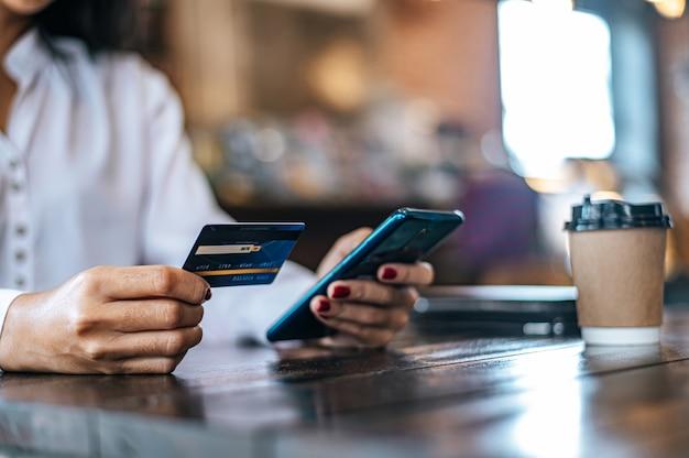 Pague los productos con tarjeta de crédito a través de un teléfono inteligente en una cafetería. Foto gratis