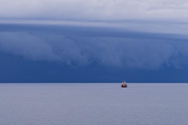 Paisaje marino con grandes nubes de tormenta sobre la superficie del mar con remolcador Foto Premium