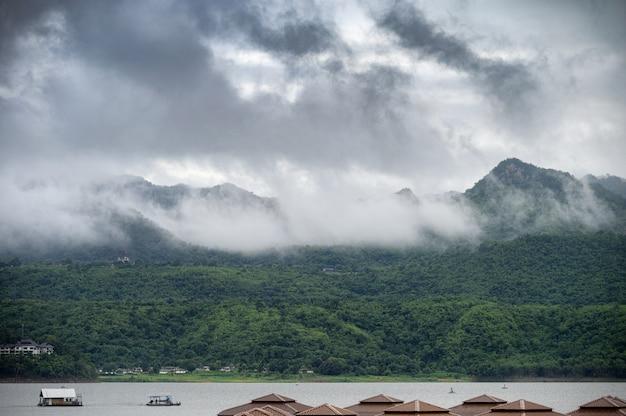Paisaje de montaña con niebla y barco navegando en presa en temporada de lluvias Foto Premium