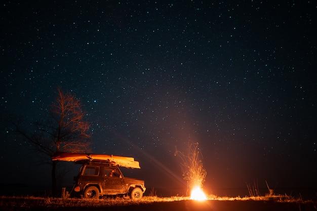 Paisaje nocturno con fogata brillante y coche Foto gratis