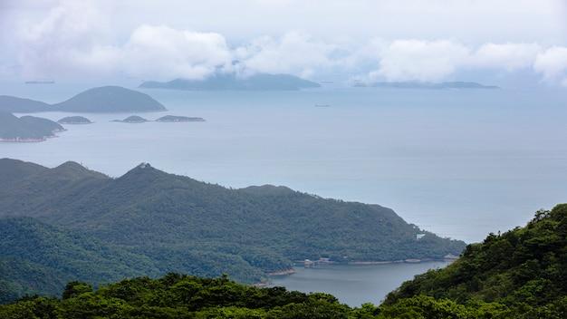Paisaje y paisaje marino de montaña y mar y envío de contenedores de carga en temporada de lluvia. Foto Premium