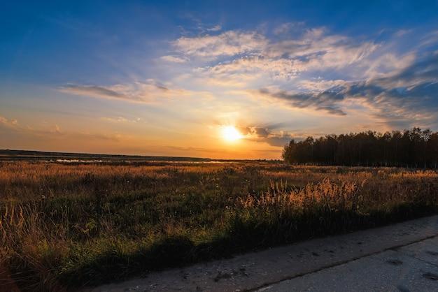 Paisaje de verano con prado y hermosa puesta de sol con bosque y río Foto Premium