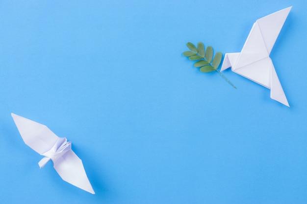 Pájaro blanco hecho de papel con rama de hoja Foto Premium
