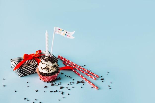 Pajitas cerca de cupcake y presente Foto gratis