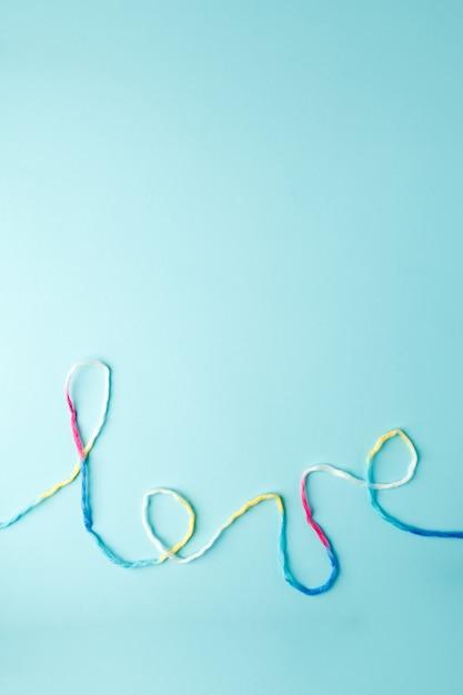 Palabra de amor escrita con letras de hilo de lana, concepto y fondo para el día de san valentín Foto Premium