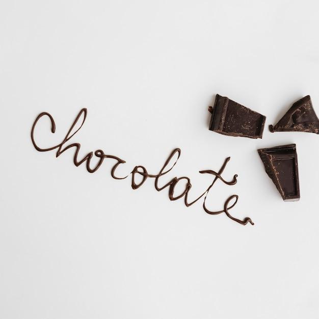 Palabra de chocolate cerca de pedazos de chocolate Foto gratis