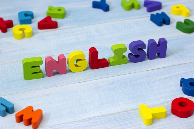 Palabra inglesa colorida de madera en fondo de madera azul. Foto Premium