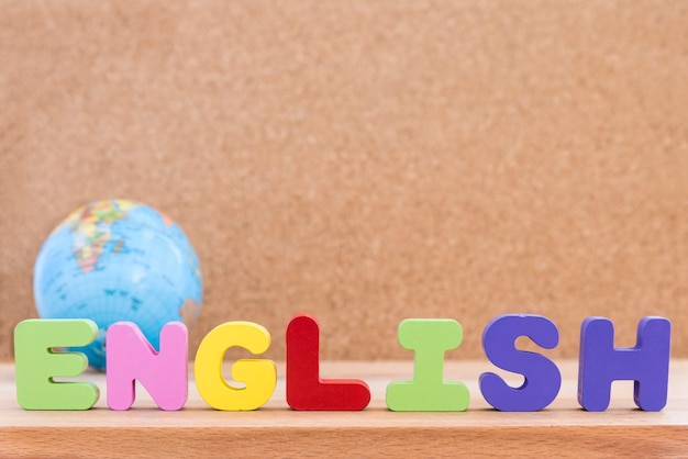 Palabra inglesa con el globo sobre fondo de madera Foto gratis