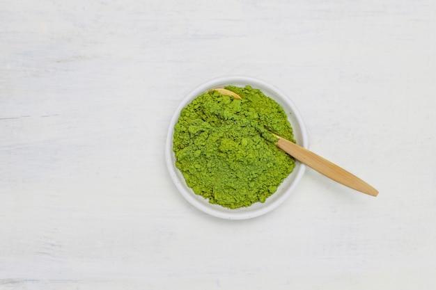 Palabra matcha hecha de té verde matcha en polvo y cuchara de bambú en blanco. copiar Foto gratis