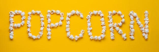 La palabra palomitas de maíz se presenta a partir de palomitas de maíz. Foto Premium