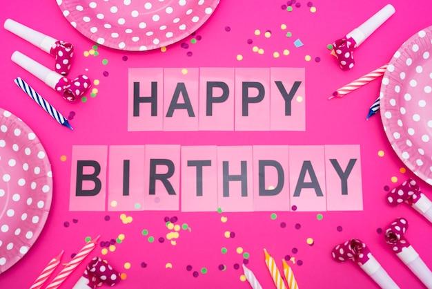 Palabras de feliz cumpleaños con platos y silbatos y velas. Foto gratis