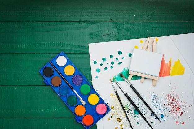 Paleta de acuarela; pinceles; mini caballete y papel dibujado a mano sobre escritorio verde Foto gratis