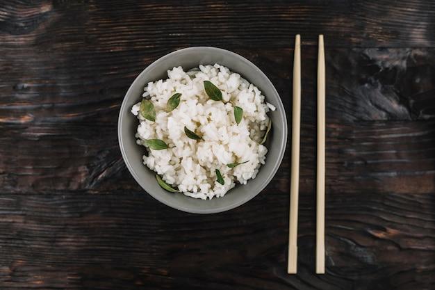 Palillos y arroz en la superficie de madera Foto gratis