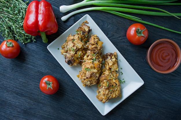 Palillos de pollo asados en una placa. Foto Premium