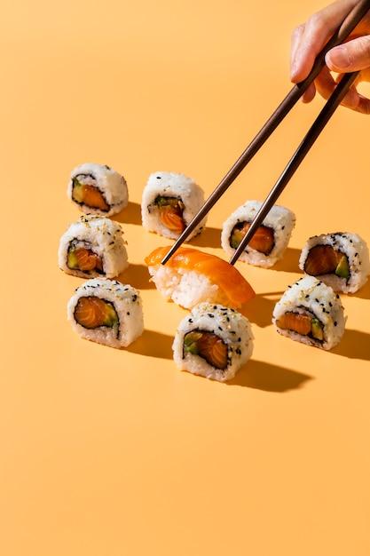 Palillos recogiendo sushi nigiri de maki rolls Foto gratis