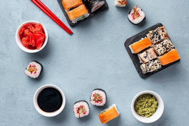 Palillos de sushi maki plano y palillos y marco de salsa de soja Foto gratis