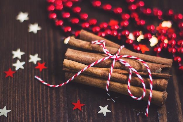 Palitos de canela navideños atados con una cuerda en una mesa festiva de madera Foto gratis