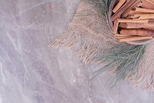Palitos de canela en una taza de madera con rama de roble alrededor Foto gratis