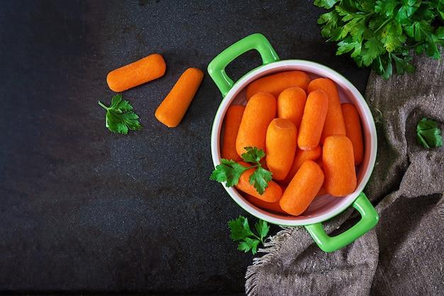 Palitos de zanahoria bebé en un tazón verde sobre una superficie negra. concepto de alimentación saludable comida vegana. vista superior. lay flat Foto gratis