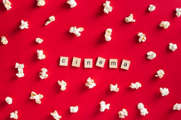 Palomitas de maíz planas sobre fondo rojo con letras de cine Foto gratis