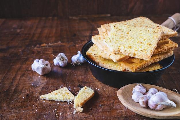 Pan de ajo crujiente en una mesa de madera Foto Premium