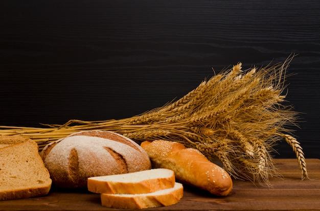 Pan blanco y de centeno, una hogaza, una gavilla en la mesa de madera, fondo negro, espacio para texto Foto Premium