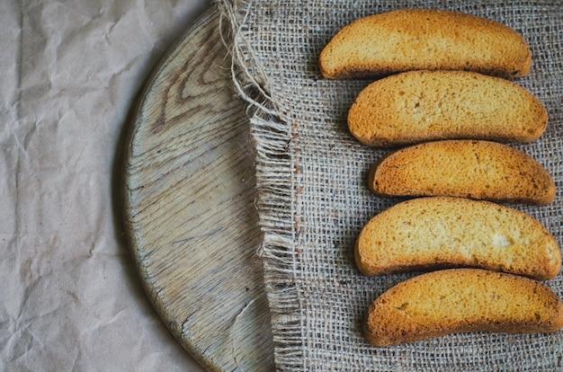 Pan blanco tostado sobre lienzo y papel de envolver vintage, tonificado y descolorido Foto Premium