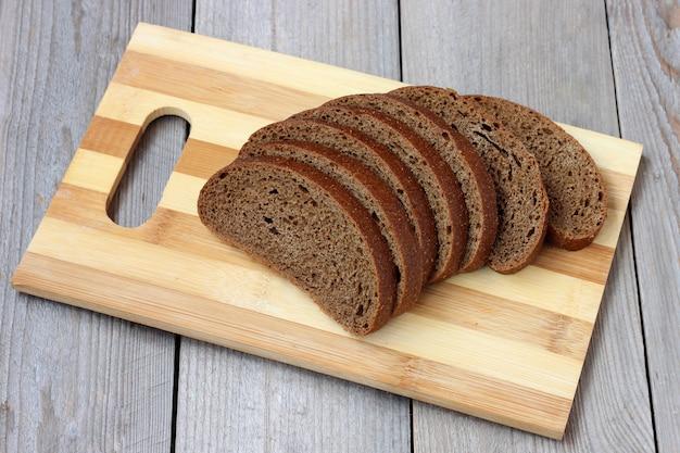 Pan de centeno, cortado en trozos, se encuentra en una tabla de cortar en la mesa. Foto Premium