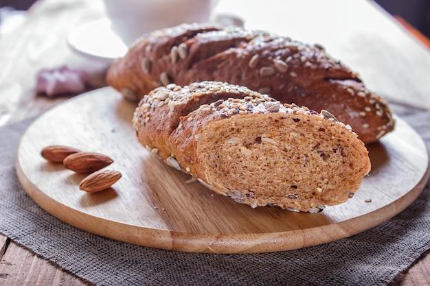 Pan de centeno con semillas de girasol, sésamo y lino sobre tabla de madera. Foto Premium