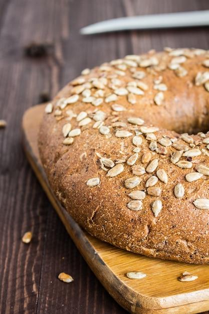 Pan de centeno con semillas de girasol en tablero de madera Foto gratis