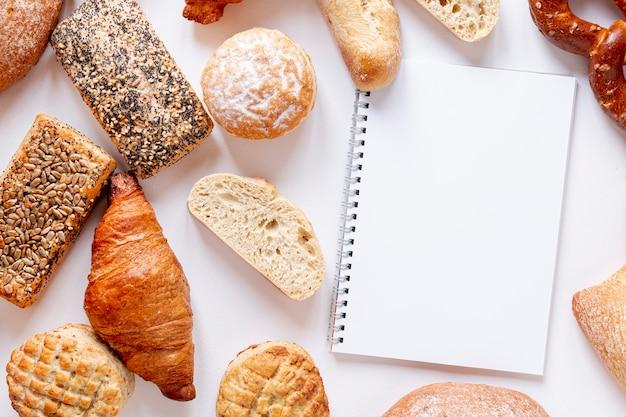 Pan y cruasanes cerca de un cuaderno Foto gratis