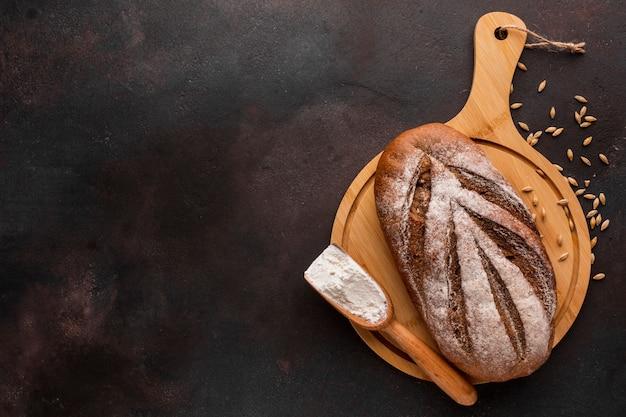 Pan crujiente sobre tabla de madera con semillas de trigo Foto gratis
