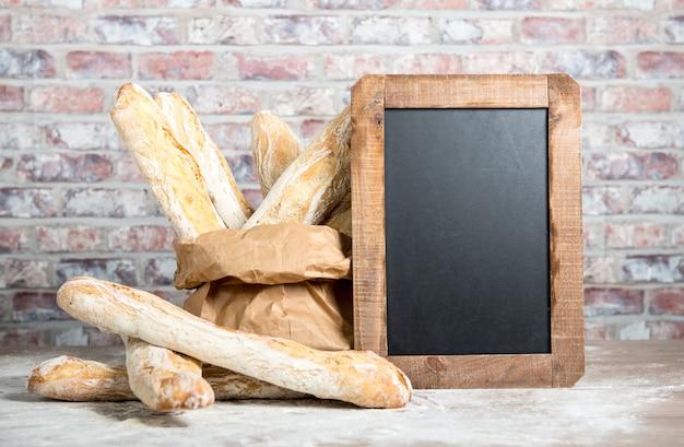 Pan francés con pizarra sobre una mesa rústica Foto Premium