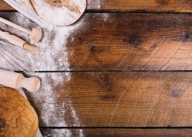 Pan y harina con equipos en mesa de madera. Foto gratis