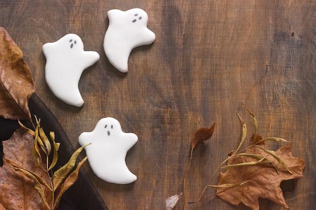 Pan de jengibre fantasma para halloween, decorado con hojas de otoño, sobre un fondo de madera. Foto Premium