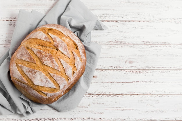 Pan en paño de cocina y vista superior de fondo de madera Foto gratis
