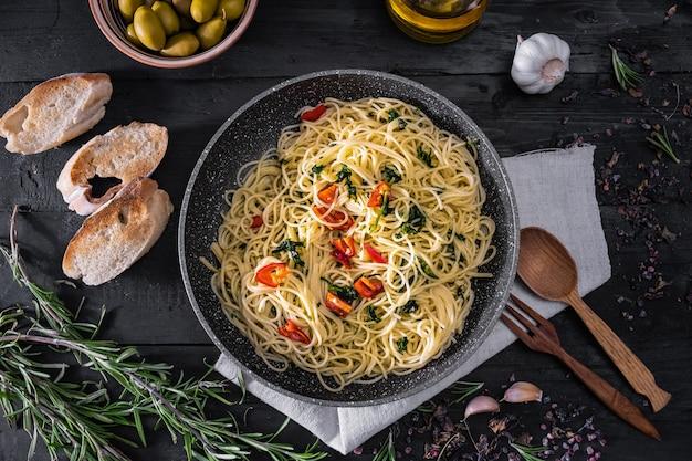 Pan de pasta italiana cocida, vista superior. endecha plana de comida tradicional de espagueti con verduras, ajo y aceitunas en superficie rústica negra Foto Premium