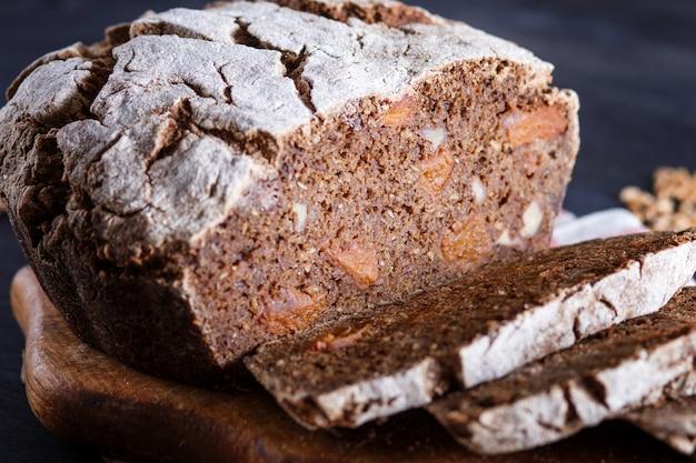 Pan rebanado casero sin levadura con centeno entero y granos de trigo sobre fondo de madera negra Foto Premium
