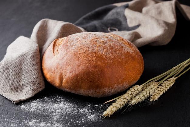 Pan recién horneado con harina y papel de cocina sobre fondo negro Foto Premium