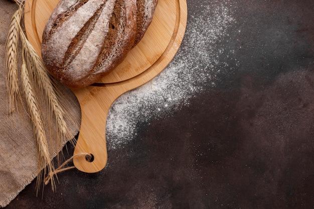 Pan sobre tabla de madera con trigo y harina Foto gratis