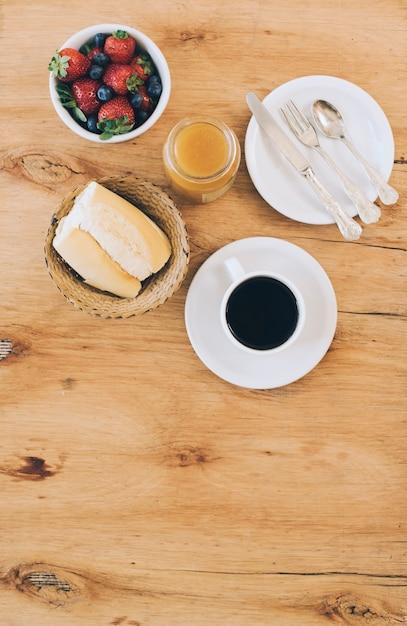 Un pan; taza de café; mermelada; bayas frescas y cubiertos en placa contra el fondo de madera Foto gratis