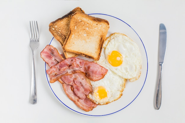 Pan tostado; tocino y medio huevos fritos en un plato de cerámica con un tenedor y un cuchillo de mantequilla aislados sobre fondo blanco Foto gratis