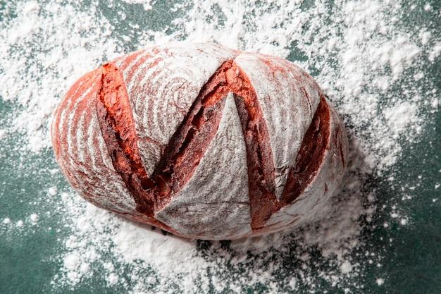 Pan tradicional dentro de la harina blanca en la mesa de piedra verde. Foto gratis